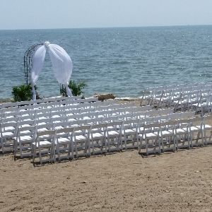 white wedding chair set up with arch on Lake Erie Beach