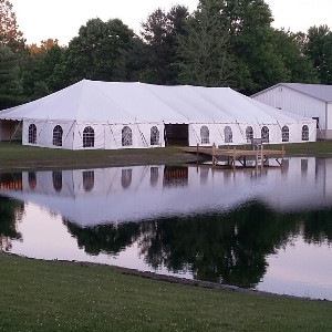 40x100 pole tent by a pond and barn