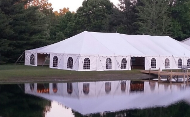 40 ft. x 100 ft. Celina Pole Tent by a Pond and Barn